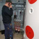 Rørlegger i telefonen foran vedfyringsanlegg i teknisk rom